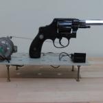 Sem título, 2010, revólver calibre 32, vidro e mecanismo elétrico, 14x30x12 cm