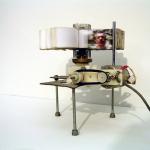 Sem título, 2002, mecanismo de videocassete, motor elétrico e 250 impressões, 12x13x12 cm