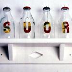 """""""Suor"""" 1997-2014, recipientes vidro, tampas metálicas, arame, letras metálicas, prateleira madeira pintada de branco, edição 5/5, 30x25x20 cm"""