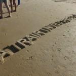 """""""A trair investimento - Block letter"""", 2015, texto moldado na areia da praia, realizado com a comunidade do Poço da Draga e os artistas da mostra """"Ocupações"""", BNB, Fortaleza, CE, foto de Ronald Duarte"""