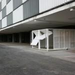 """""""Estande"""", 2007. Construção com portões automáticos em chapa de metal perfurado. Paredes basculantes e deslizantes, programadas para se moverem, a cada dois minutos, abrindo e fechando."""