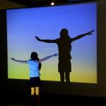 Criança brinca com a projeção que compõe a obra de Wagner Malta Tavares