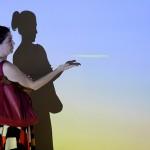 Visitante posa com a projeção que compõe a obra de Wagner Malta Tavares